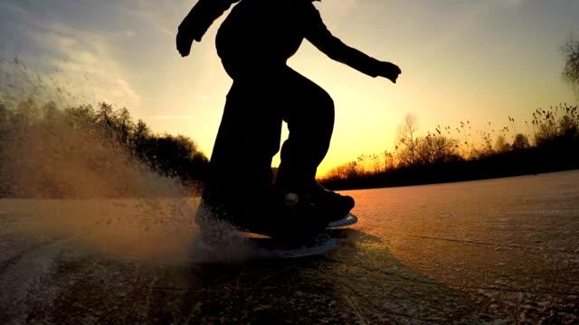 close up, low angle: nierozpoznawalny radosny człowiek rozpylający lód podczas zatrzymywania się w hokeju - łyżwa filmów i materiałów b-roll