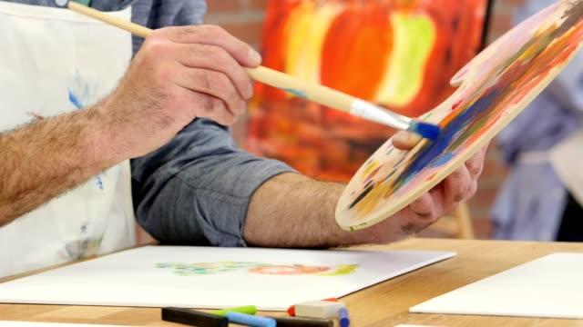 Unrecognizable male artist paints in his art studio video