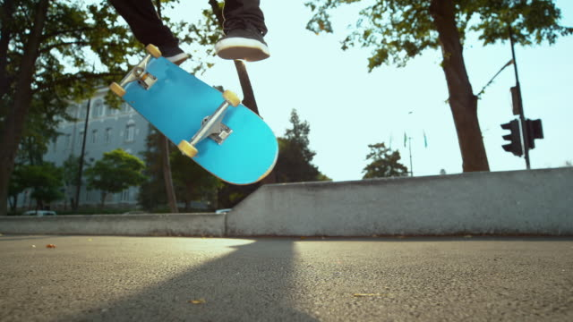 SLOW MOTION: Unrecognizable male athlete does a fakie trick with his skateboard.