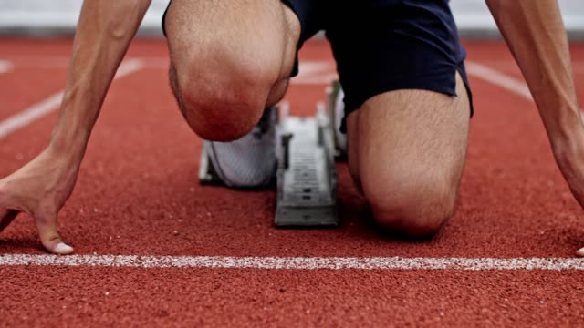 Unrecognizable Male Athlete Preparing At Starting Line. Young unrecognizable male athlete preparing at starting line for run. Track runner put his hands at starting line, starting from sprinter block. athleticism stock videos & royalty-free footage