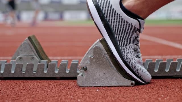 vidéos et rushes de sprinter masculin méconnaissable d'athlète commençant au bloc de sprinter. - starting block