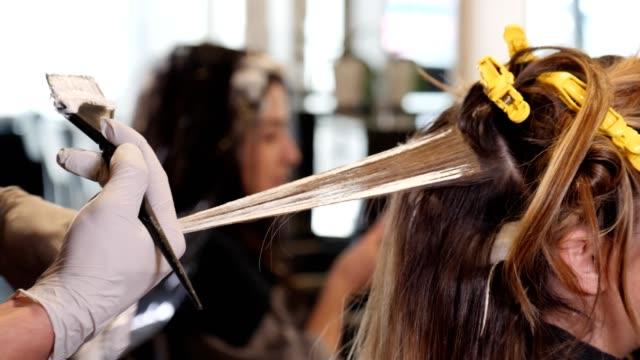 認識できない男性ヘアスタイリスト慎重に、染毛剤に半ば成人女性の髪 - 美容室のビデオ点の映像素材/bロール