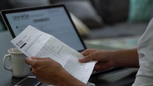 집에서 인식할 수 없는 남자가 은행 계좌 명세서를 확인 하 고 랩톱을 사용 합니다. - 검사 보기 스톡 비디오 및 b-롤 화면
