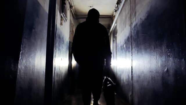 黒いジャケットを着て、カメラから離れて歩くバッグを運ぶ認識できない男の強盗 - こっそり点の映像素材/bロール