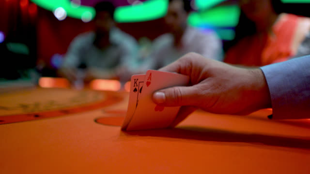 Unrecognizable man gambling at the poker table lifting his cards to look at them