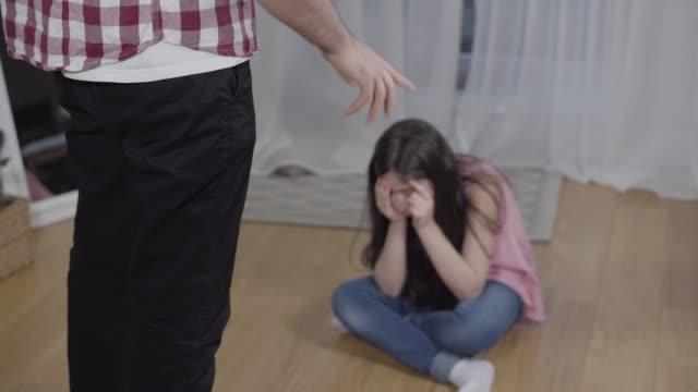 oigenkännlig man gestikulerar känslomässigt som skällde suddiga lilla mellanöstern flicka sitter på golvet. strikt far tillrätta tillrättakande dotter för dåligt uppförande. disciplin, utbildning, lydnad. - enbarnsfamilj bildbanksvideor och videomaterial från bakom kulisserna