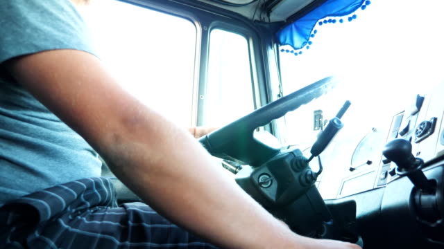 Unrecognizable man holding his hand on steering wheel and driving truck at urban road. Lorry driver rides to destination. View from the truck cab. Slow motion Unrecognizable man holding his hand on steering wheel and driving truck at urban road. Lorry driver rides to destination. View from the truck cab. Slow motion car transporter stock videos & royalty-free footage