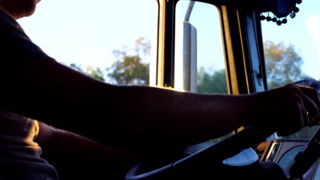 vídeos y material grabado en eventos de stock de irreconocible hombre sosteniendo sus manos en el volante y conducir un camión en la carretera en un día caliente de verano. taxi del carro adentro. lado más lenta cerca - conductor de autobús