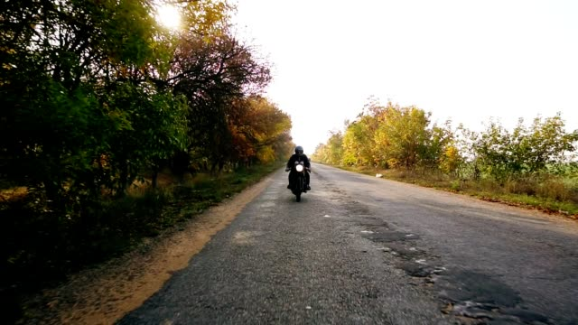 vídeos de stock e filmes b-roll de unrecognizable man in black helmet and leather jacket approaching while riding a motorcycle on a road on a sunny day in autumn. then he outruns the camera point of view and moves forward - helmet motorbike