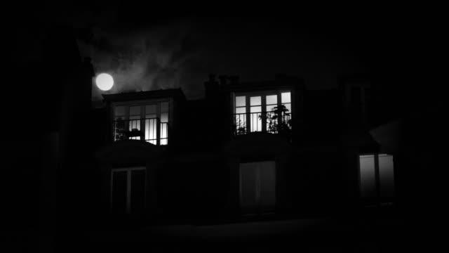 Unrecognizable Man inside mansard roof apartment building in central PAris moonlight full moon