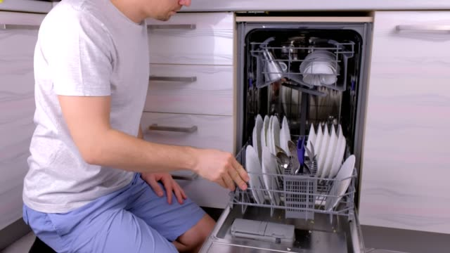 Unrecognizable man is putting a white dirty plates in the dishwasher and running it in the kitchen. video