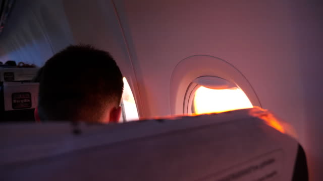 Unrecognizable man looking to airplane window during flight. Young passenger travelling by plane. Tourism or travel concept. Rear back view Close up video
