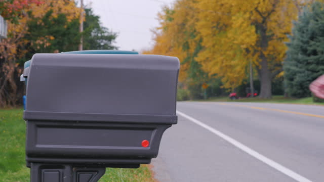 Unrecognizable man picks up the mail from the mailbox