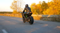 istock Unrecognizable man riding on modern sport motorbike at autumn highway. Motorcyclist racing his motorcycle on country road. Biker driving bike during trip. Concept of freedom and adventure. Rear view 1223205828
