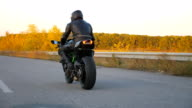 istock Unrecognizable man riding on modern sport motorbike at autumn highway. Motorcyclist racing his motorcycle on country road. Biker driving bike during trip. Concept of freedom and adventure. Rear view 1223228010