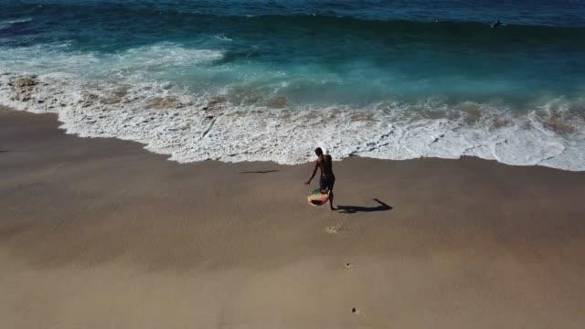 stockvideo's en b-roll-footage met onherkenbaar man loopt aan de golven die klaar zijn om te surfen - gewone snelheid