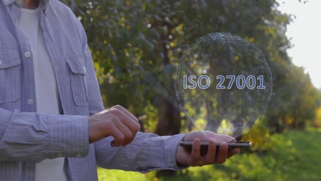Unrecognizable man shows conceptual hologram with text ISO 27001