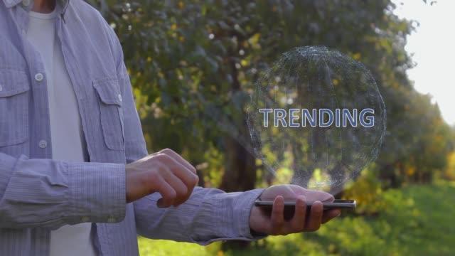 vídeos de stock, filmes e b-roll de irreconhecível homem mostra holograma conceitual com texto trending - manipulação digital