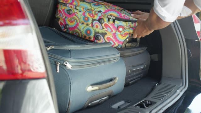 クローズ アップ: 認識できない男アンロード重いスーツケース現代の黒の suv から。 - 荷物をとく点の映像素材/bロール