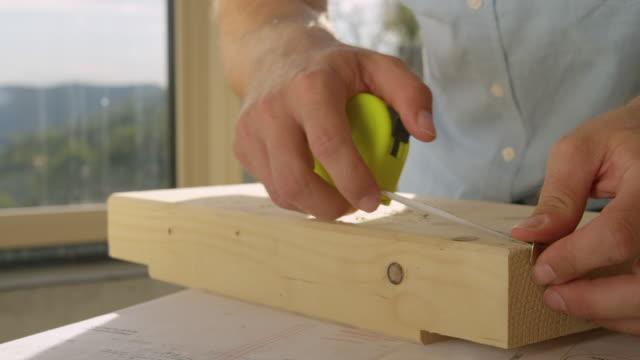 närbild: oigenkännlig man använder ett måttband för att inspektera ett block av trä. - solar panel bildbanksvideor och videomaterial från bakom kulisserna