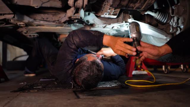 stockvideo's en b-roll-footage met onherkenbaar monteur werkt onder een auto met behulp van een hulpmiddel - arbeider