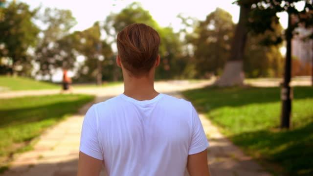 stockvideo's en b-roll-footage met onherkenbaar mannen lopen op straat - t shirt