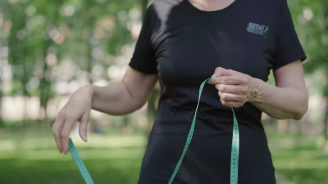 Unrecognizable mid-adult sportswoman measuring waist with tape. Confident slim Caucasian woman in sportswear standing outdoors in sunny summer park. Workout and sport concept. Unrecognizable mid-adult sportswoman measuring waist with tape. Confident slim Caucasian woman in sportswear standing outdoors in sunny summer park. Workout and sport concept. one mid adult woman only stock videos & royalty-free footage