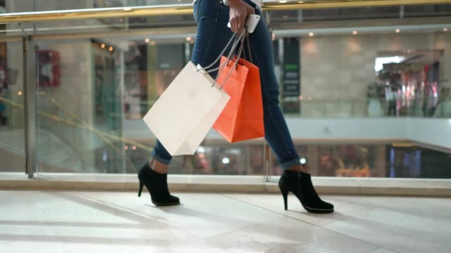 unrecognizable modern woman walking around the mall holding her shopping bags and smartphone - borsa della spesa video stock e b–roll