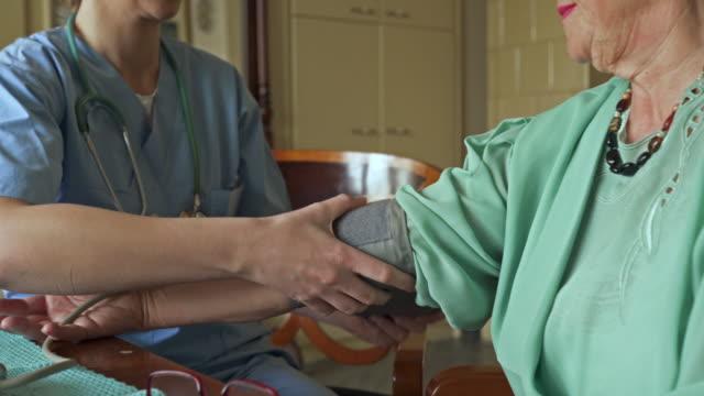 vídeos de stock e filmes b-roll de unrecognizable old woman getting her blood pressure measured by female nurse. - enfermeira