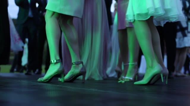 oigenkännlig folk dansar på part bröllop i festliga kläder nära upp slowmotion kväll ljus färg. kvinnliga ben i klänning designer skor kliva golvet skede ingen ansikte firande lycka glädje - dansbana bildbanksvideor och videomaterial från bakom kulisserna