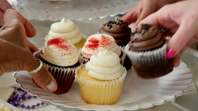 Unrecognizable people pick up cupcakes from plate