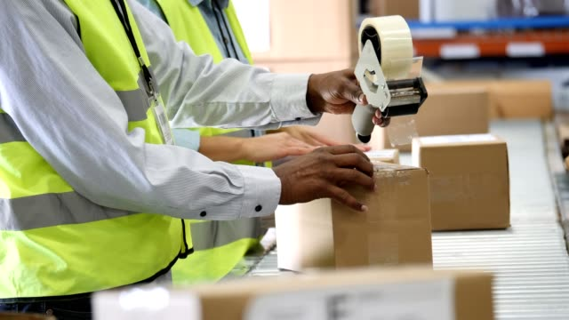 vídeos de stock e filmes b-roll de unrecognizable people seal packages in distribution warehouse - packaging
