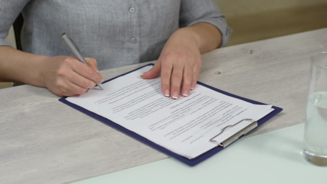 unrecognizable people signing document - vendere video stock e b–roll