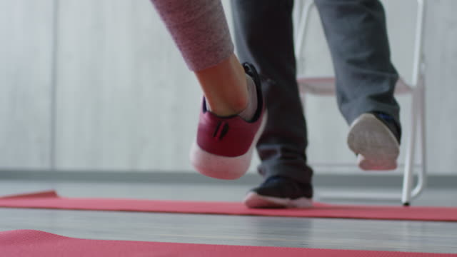 unrecognizable people stretching ankles before workout - rozgrzewka filmów i materiałów b-roll