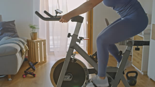 SLO MO Unrecognizable person exercising on the exercise bike Slow motion dolly shot of an unrecognizable person exercising on the exercise bike at home. Conceptual shot of the self isolation time. Shoot in 8K resolution. exercise bike stock videos & royalty-free footage
