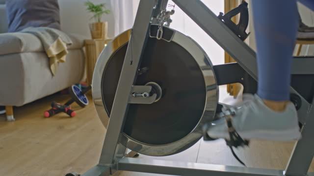 slo mo unrecognizable person exercising on the exercise bike - sprzęt sportowy filmów i materiałów b-roll