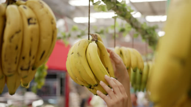 Unrecognizable person hanging bananas at a farmer's market stall