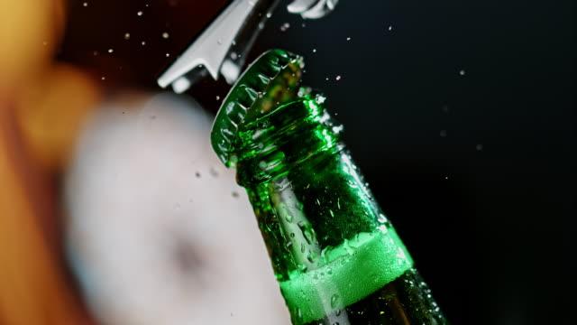 vidéos et rushes de slo mo méconnaissable personne ouvrant une bouteille de bière - main service