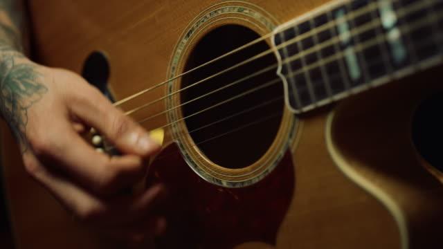 oigenkännlig person som spelar akustisk gitarr i mörk inspelningsstudio. - akustisk gitarr bildbanksvideor och videomaterial från bakom kulisserna