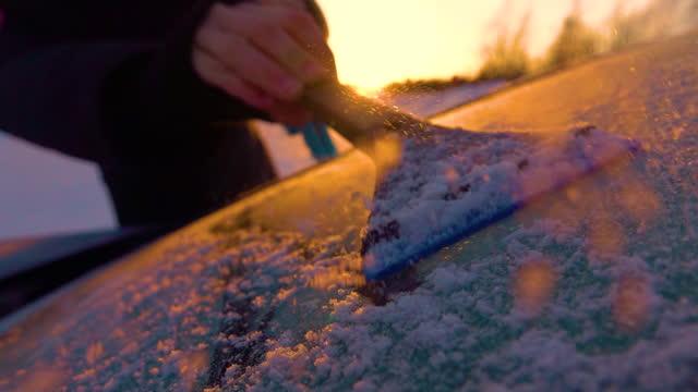 vidéos et rushes de macro : une personne méconnaissable gratte le pare-brise de voiture congelé à l'aide d'une spatule en plastique. - raclette