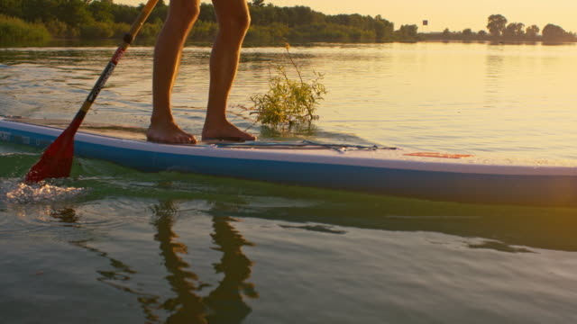 SLO MO Unrecognizable person stand-up paddleboarding video