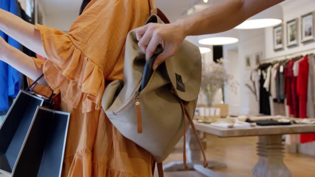 vídeos de stock e filmes b-roll de unrecognizable person stealing a smartphone from a customers bag at a clothing boutique - ladrão