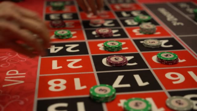 Unrecognizable players placing bets on roulette table Unrecognizable players placing bets on roulette table at the casino positioning stock videos & royalty-free footage