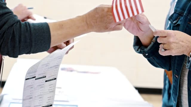 Unrecognizable polling place volunteer gives small American flag to a voter