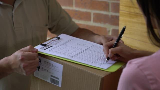 oigenkännlig post arbetare leverera låda till kvinnan hemma medan hon undertecknar ett ark - posttjänsteman bildbanksvideor och videomaterial från bakom kulisserna