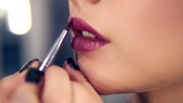 unrecognizable professional makeup artist using special brush to apply lipstick on model's lips working in beauty fashion industry - make up stock videos & royalty-free footage