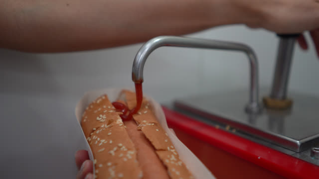 Unrecognizable saleswoman adding ketchup to hotdog at the cinema concession stand