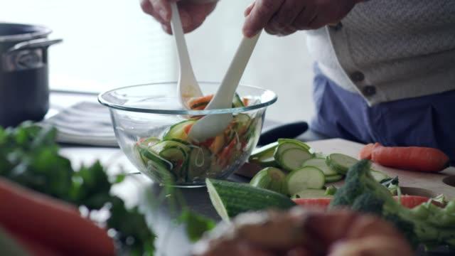 vídeos de stock, filmes e b-roll de homem sênior unrecognizable que mistura acima uma salada que está preparando - vegetarian meal