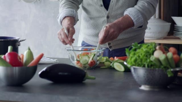 vidéos et rushes de homme aîné méconnaissable préparant une salade - diététique