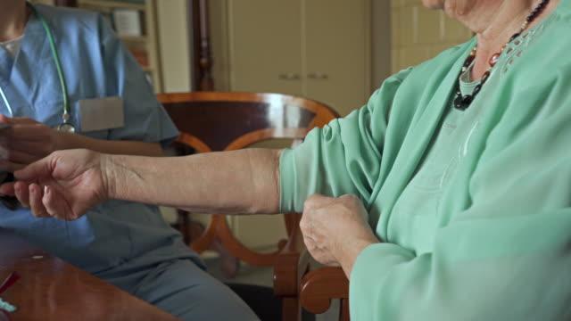 vídeos de stock, filmes e b-roll de mulher sênior irreconhecível ficando sua pressão arterial medida pelo trabalhador de saúde feminina. - assistência à terceira idade